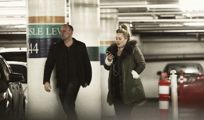 Adele texts in a parking garage